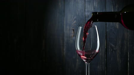 vinho : Pouring red wine into glass over dark wooden background. Slow motion.