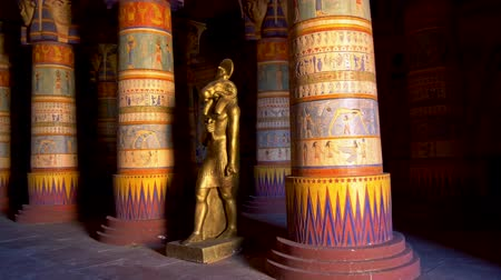 régészet : Egyptian palace filled with colourful columns and a statue of Khnum, the ram-headed Egyptian god of the source of the Nile. 4K, UHD Stock mozgókép