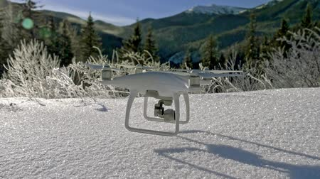 unmanned aircraft : Slow motion scene of a drone hanging in the air just above the snowy ground in the winter mountains. Shooting winter landscape concept