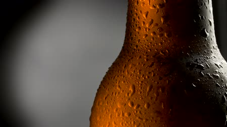ale : Cold beer bottle with water drops. Close up shot of beer over dark background with rotation. UHD 4K
