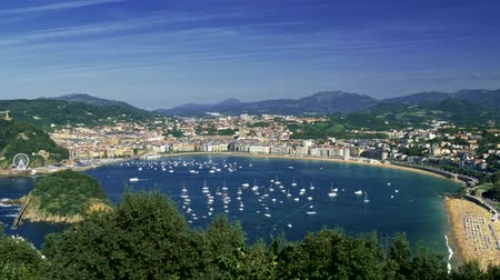 basque : Panorama of boats, beaches and the city at the Bay of Biscay in San Sebastian, Basque Country, Spain. Summer landscape with blue skies, green lush flora and a coast of the Atlantic ocean. 4K, UHD Stock Footage