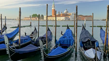kötött : Venice, Italy. Shore-bound gondolas covered with blue tarp. St Marks Basilica and bell tower are seen in the background. Gimbal shot. 4K, UHD Stock mozgókép