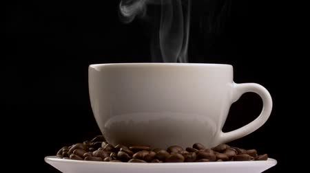 martwa natura : Rotating shot of coffee cup with steam and coffee beans. Slow motion, black background Wideo