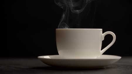 vapour : Steam slowly rising from a cup of hot coffe. Dark background Stock Footage
