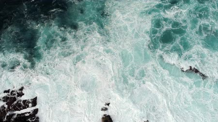 formação rochosa : Fierce stormy waves, covered with foam, striking the rocky coast with great power. Raging turquoise-colored ocean shot from top. Aerial shot, UHD Stock Footage