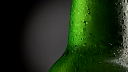 advertizing : Wet green beer bottle close-up. High quality advertizing shot of a rotating bottle of beer, covered with water drops. Black and gray background, 4K