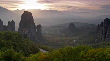 kalambaka : Scenic sunset in the mountains and a valley in Meteora, Greece. This is a place of one of the largest and most precipitously built complexes of Eastern Orthodox monasteries, second in importance only to Mount Athos. Panoramic shot, UHD Stock Footage