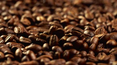 Roasted golden-brown flavorous coffee beans falling from above onto a wide pile of coffee beans. Slow motion shot