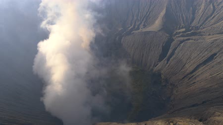 Big cloud of smoke coming from an active volcano. Crater of Bromo volcano in Bromo Tengger Semeru National Park, East Java, Indonesia. Tilt shot, 4K