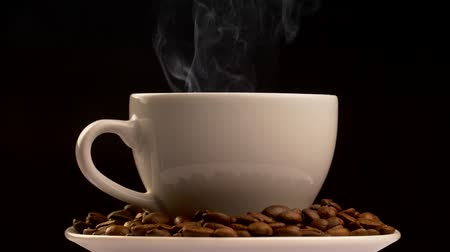 fincan tabağı : Cup of hot beverage standing on a saucer filled with brown roasted coffee beans. Gray steam is coming from the cup. Black background, slow motion shot