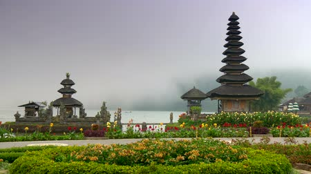Bali, Indonesia. Pura Ulun Danu Bratan Temple surrounded by beautiful flowers with mist covered water in the background. Pura Bratan is a water temple of shaivism (worship Shiva). 4K