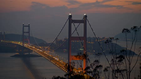 Hong Kong, China. Scenic evening cityscape of Tsing Ma Bridge and a car traffic on it. Built in 1997, Tsing Ma Bridge connects two Hong Kong islands - Tsin Yi and Ma Wan. Panning shot, 4K