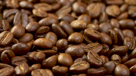Shiny and fragrant brown roasted coffee beans on a rotating panel. Background close-up, UHD