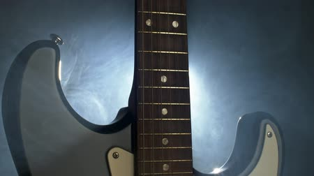 Shining electric guitar in the smoke. Close-up shot with a back light, UHD