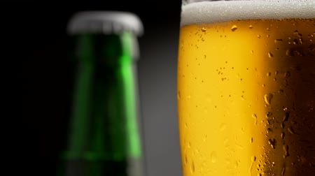 craft beer : Rotating golden foamy beer glass covered with waterdrops. Green beer bottle in the background. Close-up shot, 4K Stock Footage