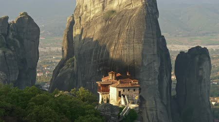 Monastery built on a vertical Meteora rock formation in Thessaly, Greece. Meteora is one of major Orthodox Christian places in the world. Tilt shot, 4K