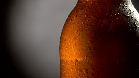 Beer bottle covered with waterdrops on a grey and black background. Close-up shot, 4K Stock mozgókép