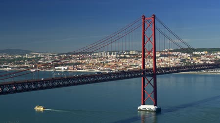 lizbona : Lisbon, Portugal. Car traffic on the 25 de Abril Bridge across the Tagus river during a bright sunny day. 4K
