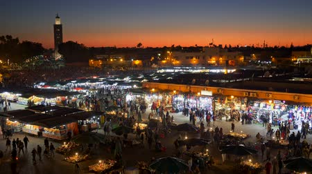 марокканский : Marrakesh, Morocco. Post sunset evening shot of crowds of people going through the marketplace at Jemaa el-Fnaa square. UHD Стоковые видеозаписи