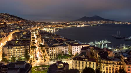 Night view of Naples, Italy. Evening time lapse of illuminated Naples with old houses, traffic and vesuvius volcano