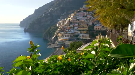 Positano, Amalfi Coast, Salerno, Italy at spring time. Crane shot of Positano village at sunset lights, yellow flowers on foreground. UHD, 4K