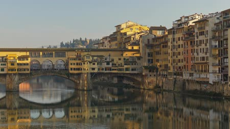 Florence, Italy. Panoramic shot of the Ponte Vecchio bridge. Its Medieval bridge over the Arno River. The bridge has shops situated on it. 4K Stock mozgókép