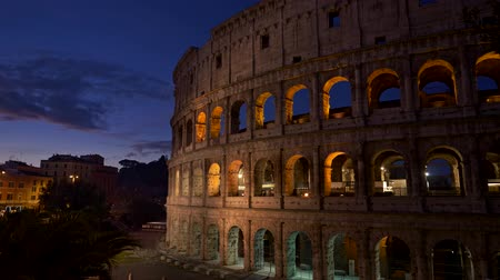 Rome, Italy. Illuminated Colosseum after sunset. Panning shot, UHD Стоковые видеозаписи