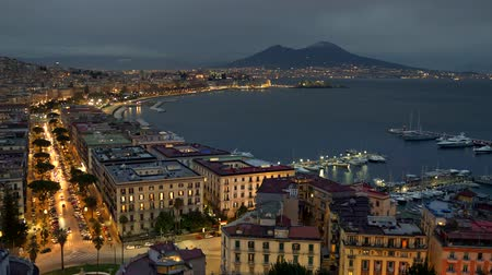 Naples, Italy. Evening city car traffic and the sea bay with a view of Vesuvius volcano. Panoramic shot, 4K