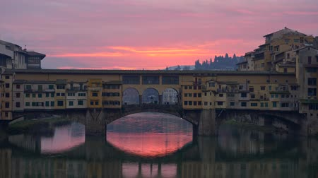 Florence, Italy. The Ponte Vecchio bridge during sunrise. Panning shot, UHD Stock mozgókép