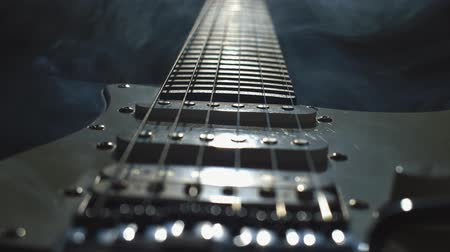 Electric guitar in the smoke close-up. Slow adjustment of focus on guitar pickups. 4K