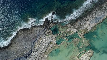 Waves striking against a rocky coast of Mediterranean Sea in Greece. Town down aerial shot, UHD