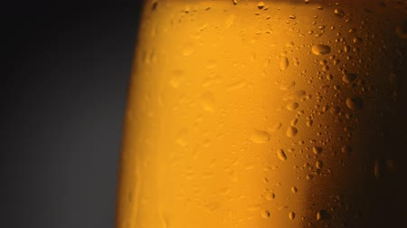 Rotating wet mug of light beer against black and gray background. Close-up shot, UHD