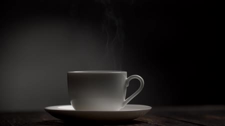 martwa natura : Steam coming from a white cup standing on a saucer on a wooden table against a gray and black background. Slow motion shot Wideo