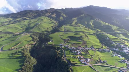 sao miguel : Flying over a village on the green Portuguese Sao Miguel Island in the Azores during a beautiful sunny morning. Aerial shot, 4K