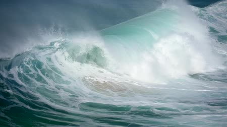 波 : Huge ocean sea waves sliding the surface of water. Foamy turquoise wave during stormy weather. Slow motion shot