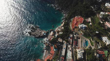 positano : Flying over the Amalfi coast of Capri Island, Italy. Turquoise waters of Tyrrhenian Sea with reflection of sun are washing the coast. Aerial shot, UHD Stock Footage