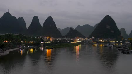 skalní útes : Colorful lights reflections in waters of Li River in Yangshuo, China during dusk. Famous crags (rocks, cliffs) of Yangshuo are seen in the background. 4K