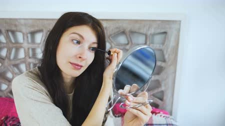 colocando : Beautiful woman holding a mirror and drawing eyebrows on face - make up concepts Vídeos