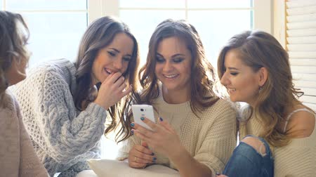 śmiech : four beautiful girls discuss smile sitting on window. Girlfriends having fun and laugh in bedroom Wideo