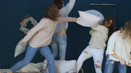 ostoba : Four beautiful girls fight pillows each other on bed slowmotion Stock mozgókép