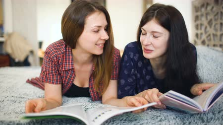 časopis : Two young woman friends are watching magazine on bed in bedroom at home