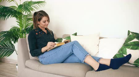 релаксация : Happy teen girl resting on sofa at the living Room while reading her favorite novel book at home Стоковые видеозаписи