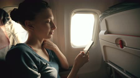 letadlo : Tourist woman sitting near airplane window at sunset and using mobile phone during flight