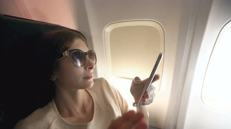 использование : Tourist woman sitting near airplane window at sunset and using mobile phone during flight