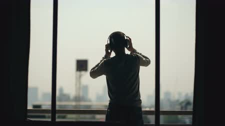 break dance : Silhouette of young man dancing ad listening music in wireles headphones stand on hotel room balcony