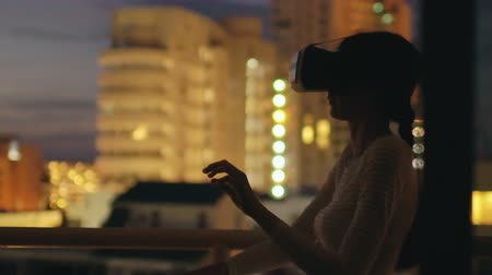 slomo : Slow motion of young woman on rooftop terrace using virtual reality headset and having VR experience at night
