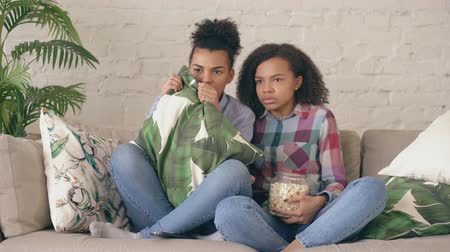 afro amerikan : Two mixed race curly girl friends sitting on the couch and watch very scary movie on TV and eat popcorn at home