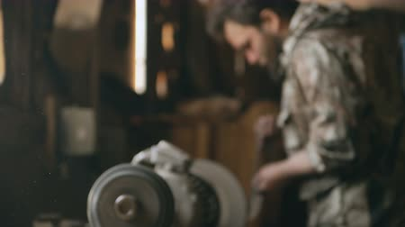 demirli : Dust fly in air on blurred background with bearded young man blacksmith manually polish metal knife on grinding machine in traditional smithy Stok Video