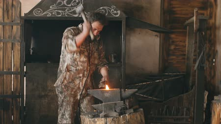 equipamento : Slowmotion of bearded young man blacksmith manually forging hot metal on the anvil in smithy with spark fireworks Vídeos