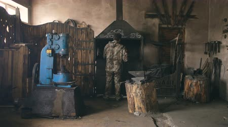 ağarmış : Bearded young man blacksmith using industrial press for steel arms manufacture at smithy workshop Stok Video